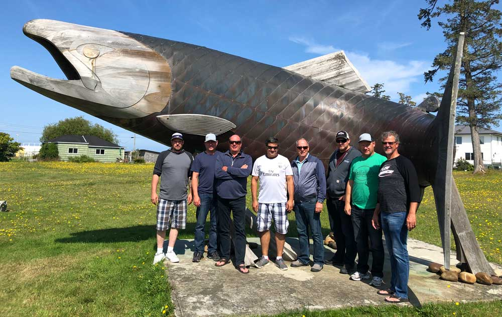 Men standing in front of giant salmon sculpture in BC
